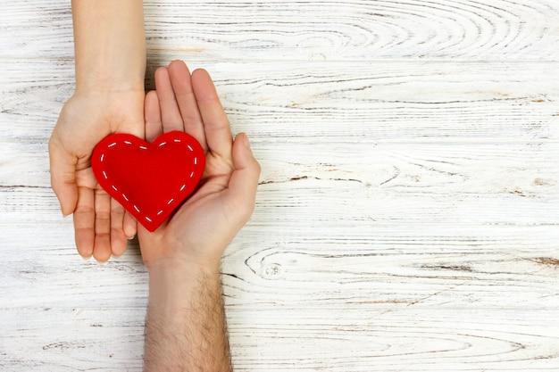Aiuto, cuore in mano su fondo di legno. concetto di giorno di san valentino. copia spazio Foto Premium