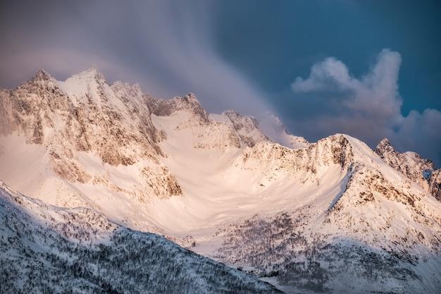 Alba dorata sulla montagna della neve con le nuvole che soffiano sulla cresta Foto Premium