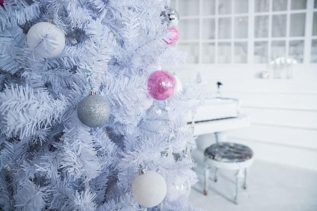Albero di natale bianco decorato con ornamenti d'argento e rosa al pianoforte Foto Premium
