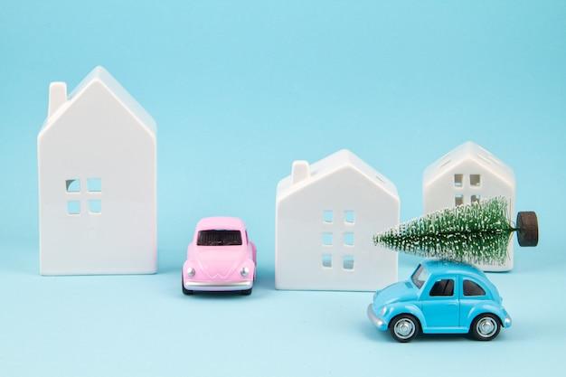 Albero di natale carring della piccola automobile del giocattolo sopra il tetto. feste sesonal, biglietto di auguri Foto Premium