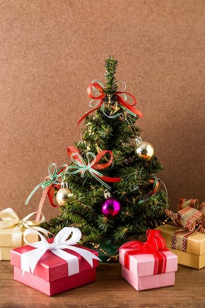 Albero di natale e contenitore di regalo sul fondo della tavola in legno Foto Premium