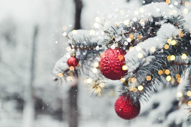 Albero di natale festivo decorato con palline di vetro rosse giocattolo con riflessi dorati. paesaggio invernale con neve e alberi di natale. Foto Premium