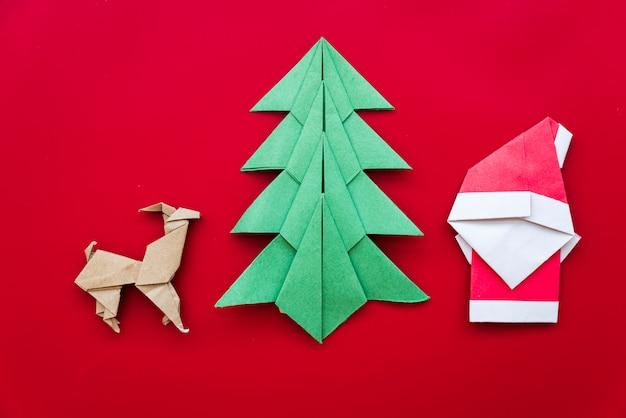 Albero di natale; renna; origami di carta babbo natale su sfondo rosso Foto Gratuite