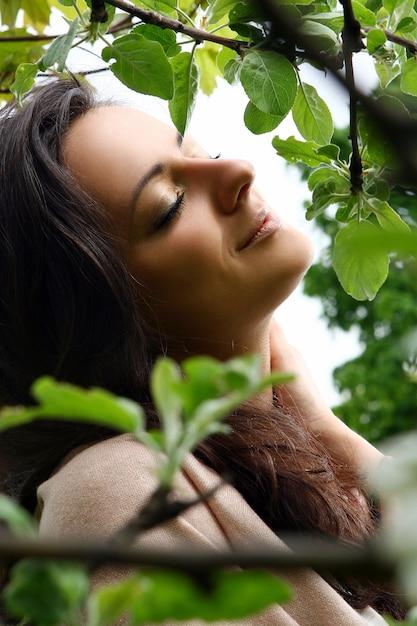 Albero sbocciante facente una pausa della bella donna nel parco verde Foto Gratuite