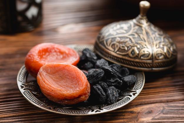 Albicocca secca e uva passa nera sul piatto metallico con coperchio sullo scrittorio di legno Foto Gratuite