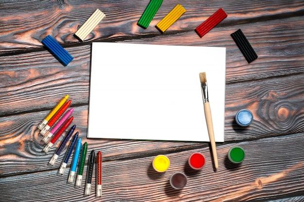 Album da disegno, pennello, pastelli a cera, colori a dita, plastilina, fondo rustico Foto Premium