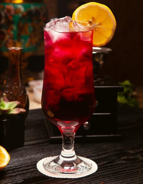 Alcool rosso cocktail in vetro con cubetti di ghiaccio e fetta di limone Foto Gratuite