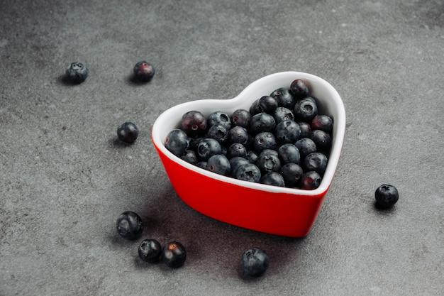 Alcune olive nere in un cuore rosso hanno modellato la ciotola su fondo grigio, vista dell'angolo alto. Foto Gratuite