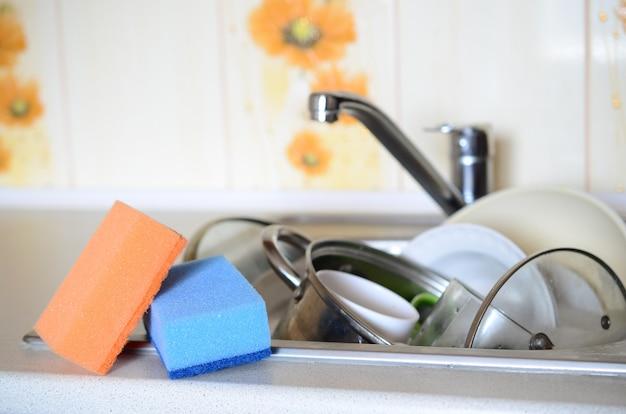 Alcune spugne si trovano sullo sfondo del lavandino con piatti sporchi Foto Premium