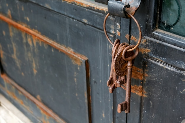 Alcune vecchie e arrugginite chiavi a catena su una porta rustica Foto Premium
