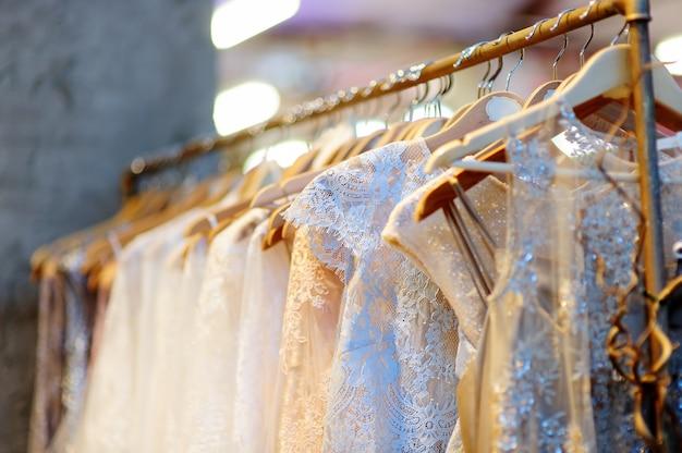Alcuni bei vestiti da sposa su una gruccia. abiti per la sposa o le damigelle Foto Premium