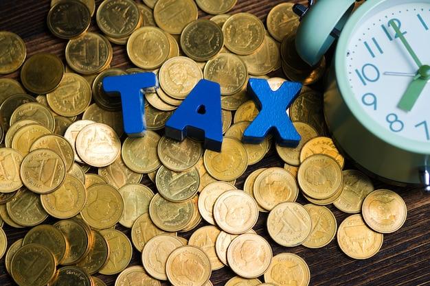 Alfabeto fiscale con pila di monete e sveglia vintage su legno Foto Premium