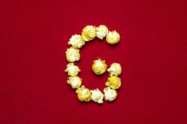 Alfabeto inglese da popcorn al cinema. lettera g. sfondo rosso per il design Foto Premium