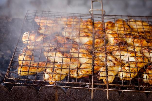 Ali di pollo alla griglia su una griglia con il fumo per la festa del cortile. Foto Premium