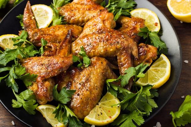 Ali di pollo arrosto con prezzemolo e limone Foto Premium