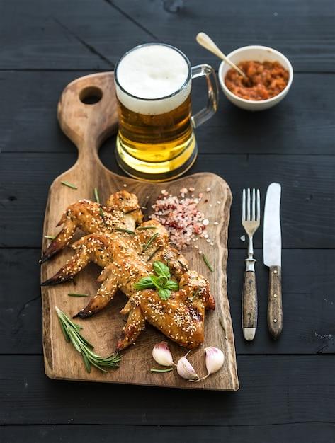 Ali di pollo fritto sul bordo di servizio rustico, salsa di pomodoro piccante, erbe e boccale di birra leggera Foto Premium