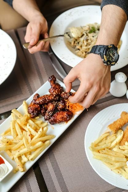 Ali di pollo mangiatrici dell'uomo del barbecue di vista laterale con le fritture e l'insalata sulla tavola Foto Gratuite