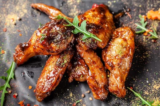 Ali e cosce di pollo al forno in salsa di senape al miele. Foto Premium