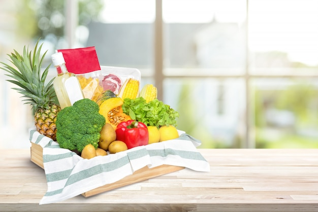Alimenti freschi e verdure in scatola di vassoio di legno sul controsoffitto della cucina Foto Premium