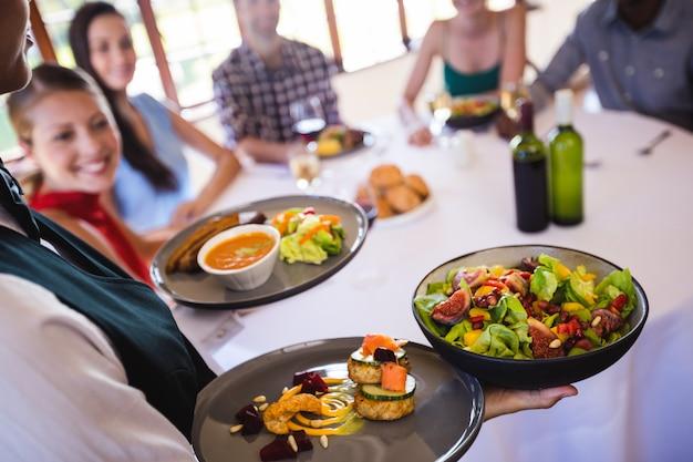 Alimento della tenuta della cameriera di bar sul piatto in ristorante Foto Premium