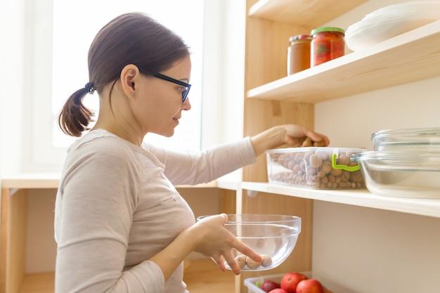 Alimento di raccolto della donna adulta dall'armadio di stoccaggio in cucina Foto Premium