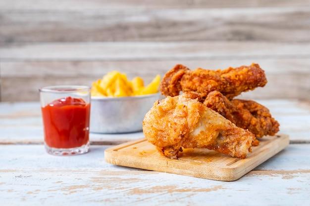 Alimento e patate fritte di pollo fritto su una tavola di legno Foto Premium