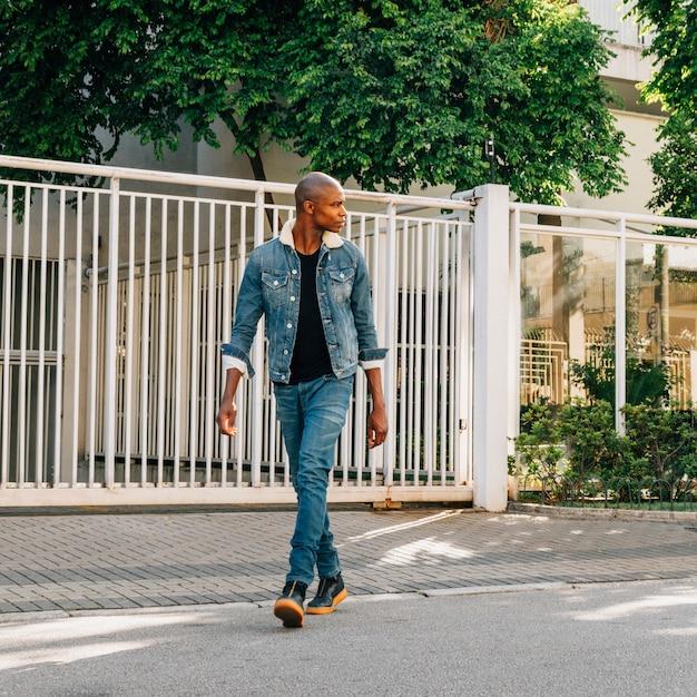 Alla moda bel giovane africano che attraversa la strada Foto Gratuite
