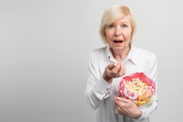 Alla nonna piace guardare i cartoni animati, i film e le diverse serie tv, come piace ai giovani. questa donna sembra una donna molto moderna. Foto Premium