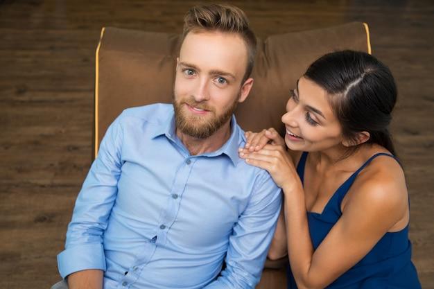 Allegro giovane coppia seduta sul divano e sorridente - Coppia di amatori che scopano sul divano ...