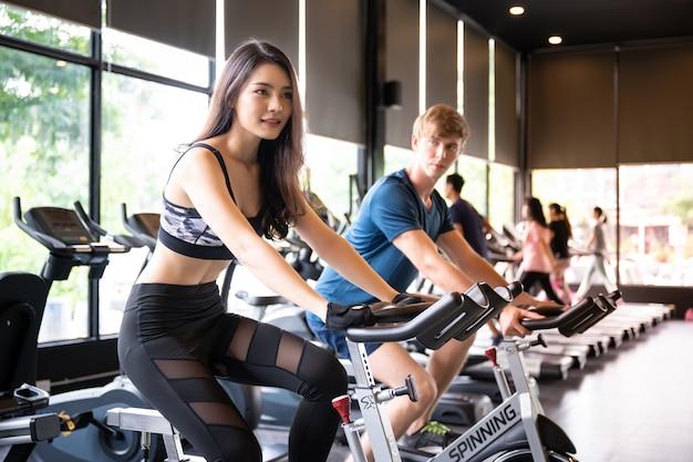 Allenamento asiatico dell'uomo e della donna alla palestra di sport ciclando la bici a macchina per cardio Foto Premium