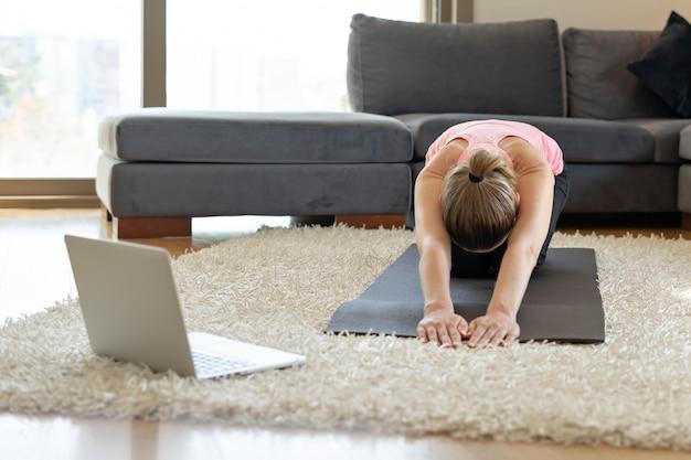 Allenamento yoga fitness online. giovane donna di fronte al computer portatile Foto Premium