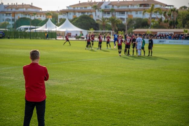 Allenatore di football americano che guarda la sua squadra nella preparazione di una partita di calcio Foto Premium