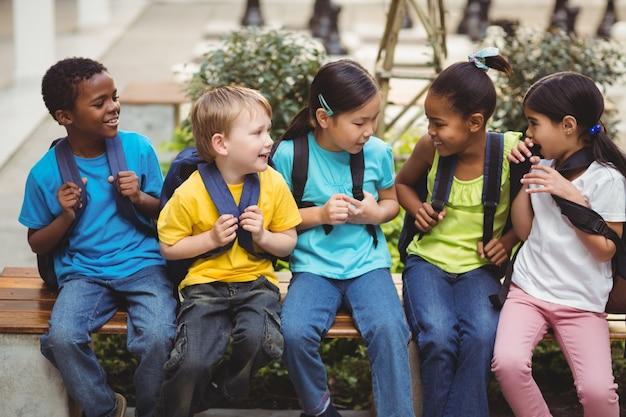 Allievi felici con le cartelle scolastiche che si siedono sul banco Foto Premium