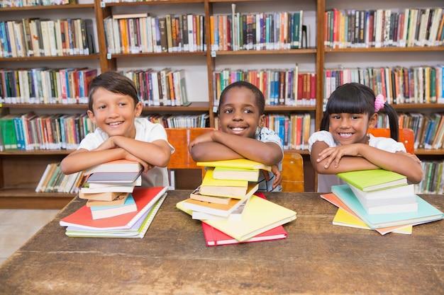 Allievi svegli che sorridono alla macchina fotografica alla biblioteca Foto Premium