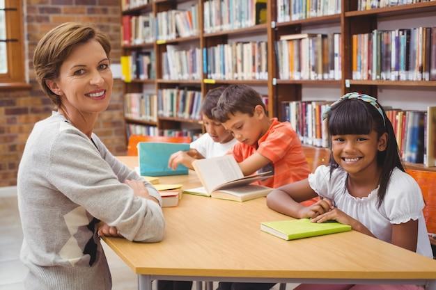 Allievi svegli e insegnante che leggono in biblioteca Foto Premium