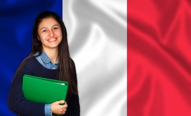 Allievo teenager che sorride sopra la bandierina francese Foto Premium