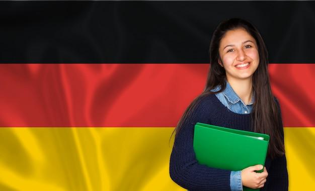 Allievo teenager che sorride sopra la bandierina tedesca Foto Premium