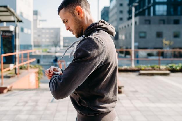 Allungamento all'aperto del giovane facendo uso di smartwatch Foto Premium