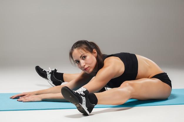 Allungamento muscolare dell'atleta della giovane donna Foto Gratuite