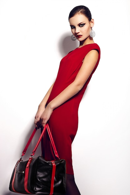 Alta moda look.glamor closeup ritratto di bella sexy elegante bruna caucasica giovane donna modello in abito rosso con borsa nera trucco luminoso, con labbra rosse, con una pelle pulita perfetta in studio Foto Gratuite