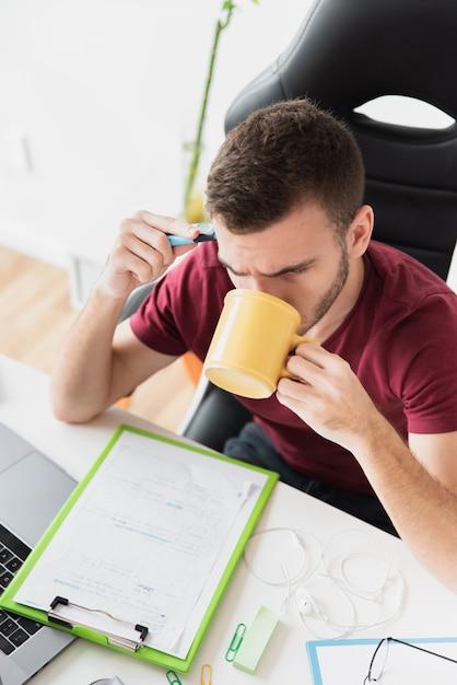 Alta vista del ragazzo pensando e bevendo un caffè Foto Gratuite