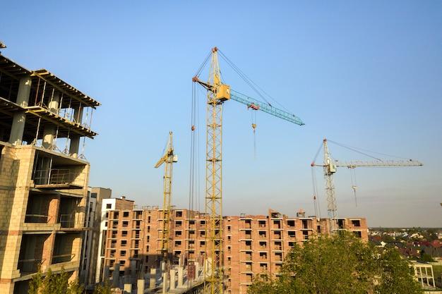 Alti edifici residenziali a più piani in costruzione. inquadramento di cemento e mattoni di case alte. sviluppo immobiliare in area urbana. Foto Premium