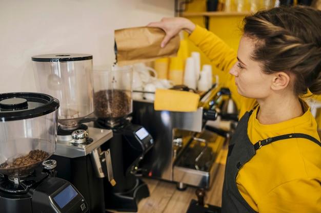 Alto angolo del barista femminile che macina caffè Foto Gratuite