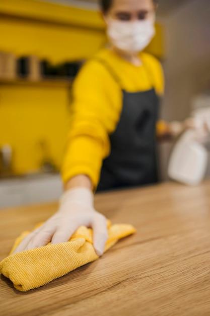 Alto angolo della superficie di pulizia defocused barista mentre indossa maschera medica Foto Gratuite