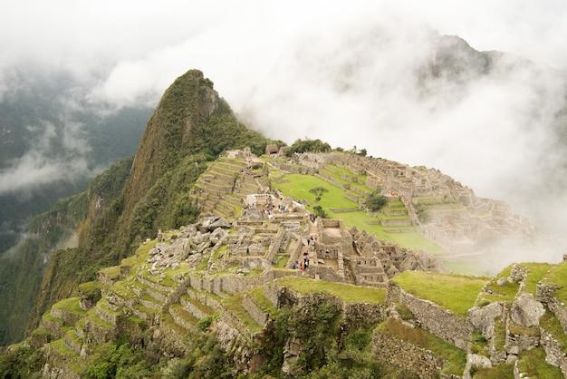 Alto angolo di bella cittadella di machu picchu circondato da montagne nebbiose a urubamba, perù Foto Gratuite