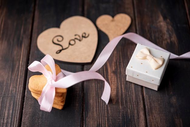 Alto angolo di biscotti a forma di cuore con presente e nastro Foto Gratuite