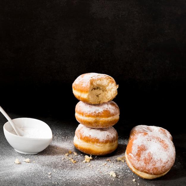 Alto angolo di ciambelle con morso e zucchero a velo Foto Gratuite