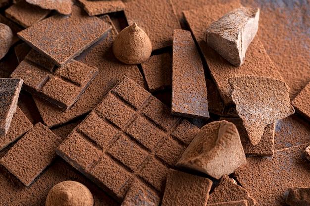 Alto angolo di cioccolato con caramelle e cacao in polvere Foto Gratuite