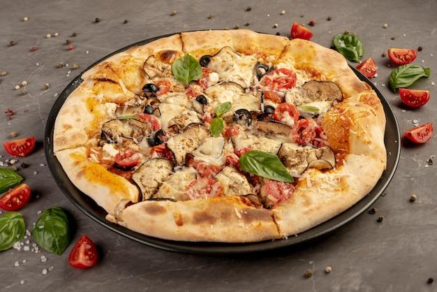Alto angolo di deliziosa pizza con pomodori e basilico Foto Gratuite