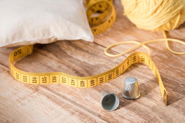 Alto angolo di ditali con filo e nastro di misurazione Foto Gratuite